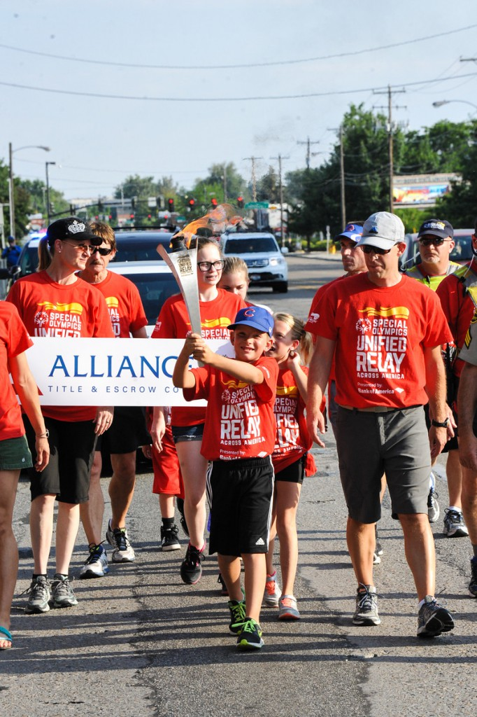 Mark Mills' son, Isaac, carries the torch for the URAA through Boise, ID.